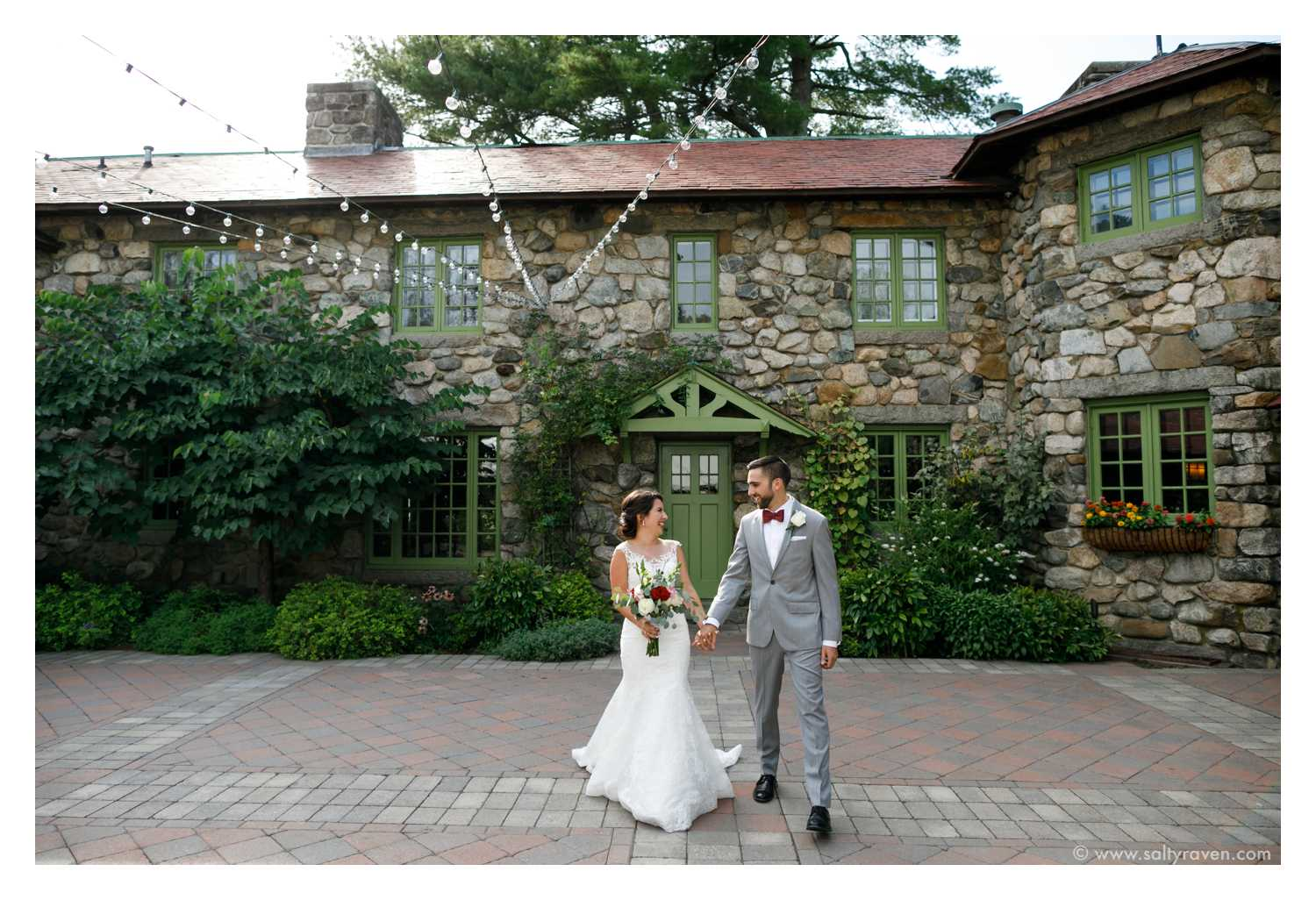 Willowdale Estate Wedding, couple walks hand in hand in front of stone building.