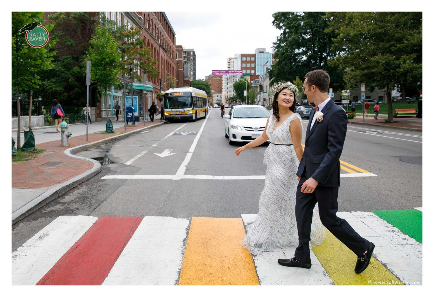A couple getting married at Cambridge City Hall crosses a rainbow crosswalk.