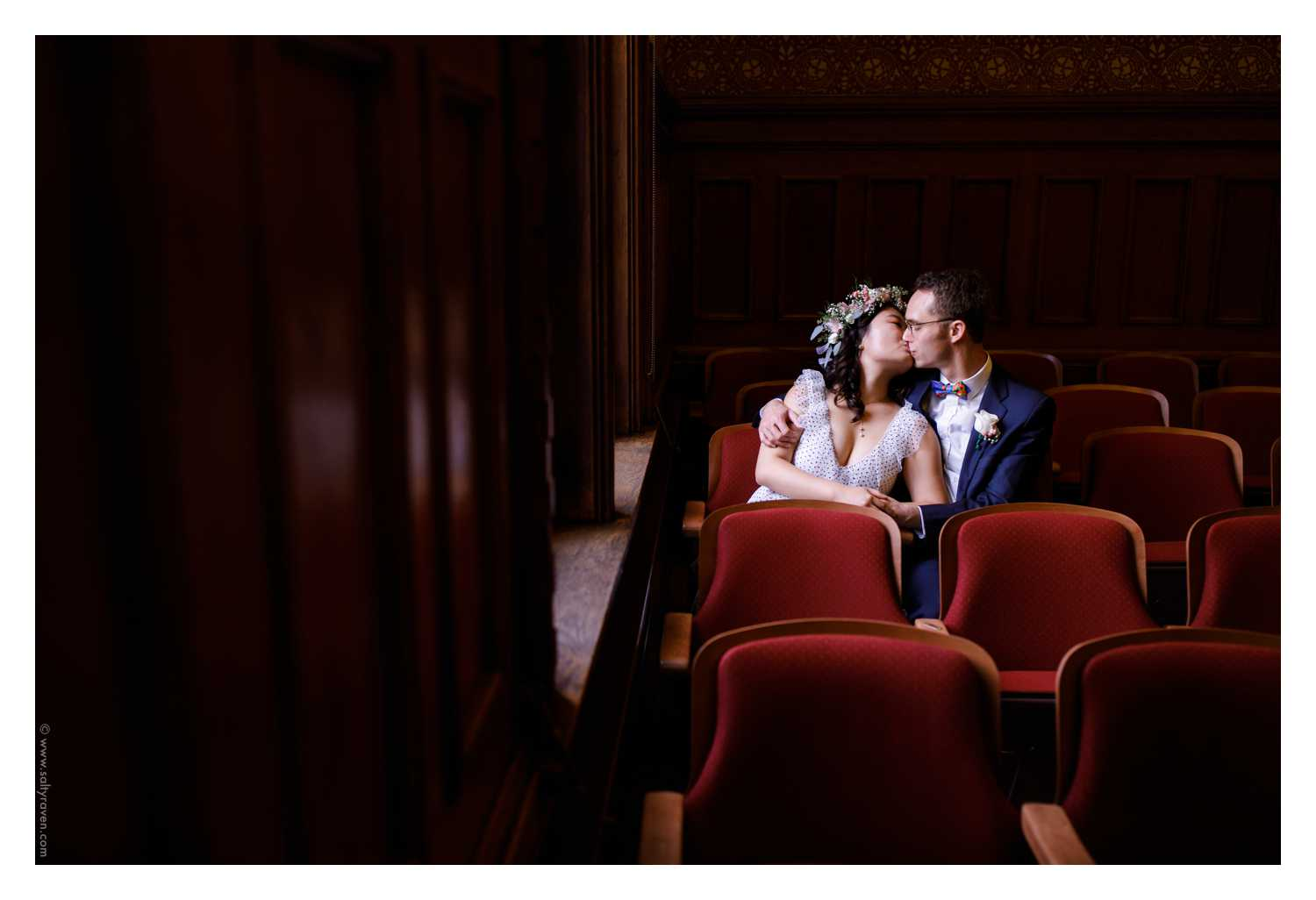 The couple steals a kiss in the red seats near a window at their Cambridge City Hall Wedding.